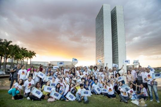 Descrição da imagem: Um grupo enorme de participantes e equipe da Escola de Gente sorrindo e mostrando placas do 2º JUVA. Ao fundo, o Congresso Nacional.