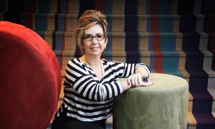 Foto mostranto Cláudia Werneck, sentada em um sofá, sorrindo para a câmera