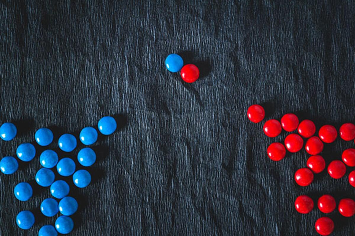 Tabuleiro com várias peças azuis à esquerda e várias peças vermelhas à direita; no centro uma peça de cada cor se encontram.