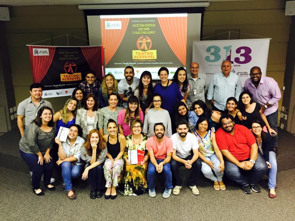 Foto mostrando a turma que participou da palestra, todos olhando para a câmera sorridentes, com o cartaz do Teatro Acessível ao fundo.