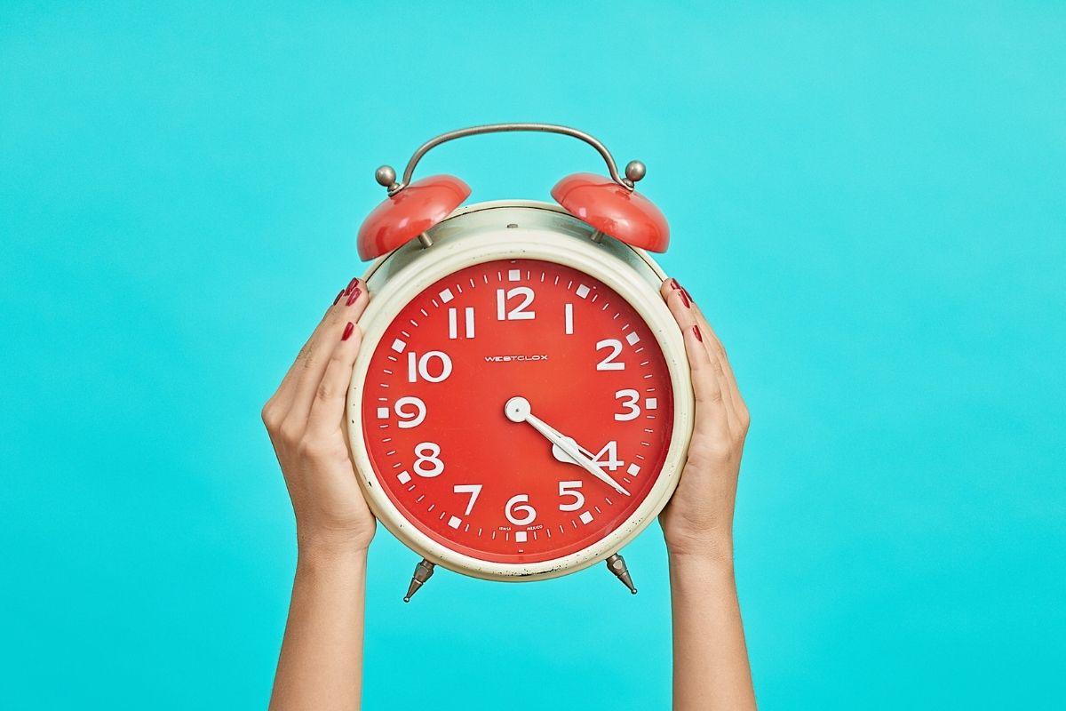 Um grande relógio despertador sendo erguido por duas mãos.