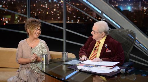 Foto mostrando Claudia Werneck, sentada no sofá, sorridente, conversando com o apresentador Jô Soares também sentado na sua mesa.