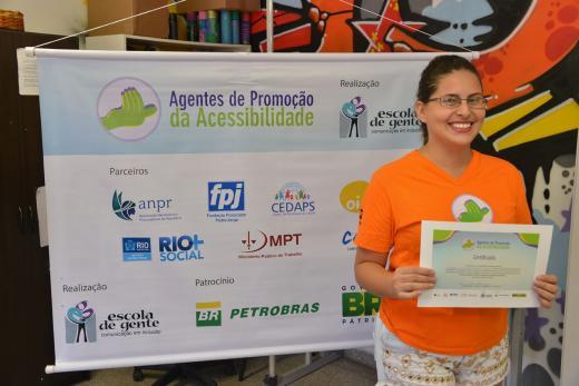"""Descrição da Imagem: Marquênia de Oliveira Barbosa Silva, em pé, segurando o certificado de conclusão do projeto """"Agentes de Promoção da Acessibilidade"""", sorri posando para foto. Atrás dela, um banner com a barra de logos dos parceiros e patrocinador."""