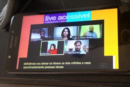 Em um smartphone, a transmissão de uma live acessível pela ONG Escola de Gente, com a tela dividida em cinco janelas com as imagens dos participantes, entre eles um intérprete de Libras e, abaixo, a legenda em tempo real.